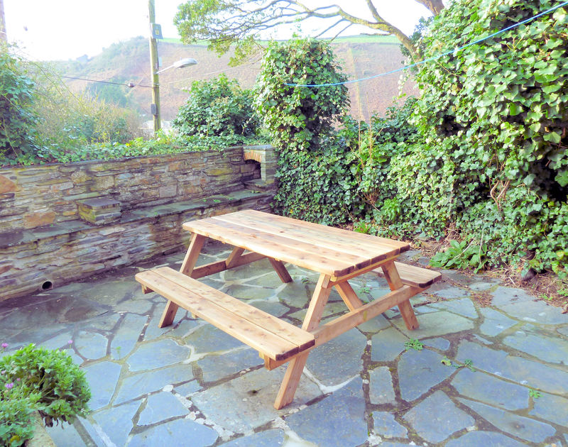 The sunny slate paved terrace with patio table at Mermaid Cottage, a charming holiday rental in Port Isaac, Cornwall.