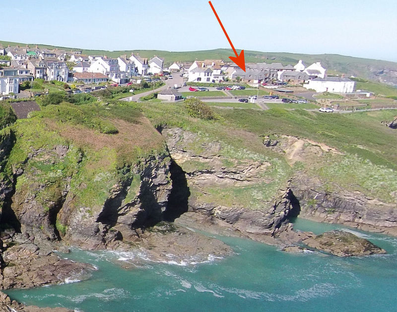 A red arrow indicating the cliffside location of Cockle Shell, a holiday house in Port Isaac, Cornwall