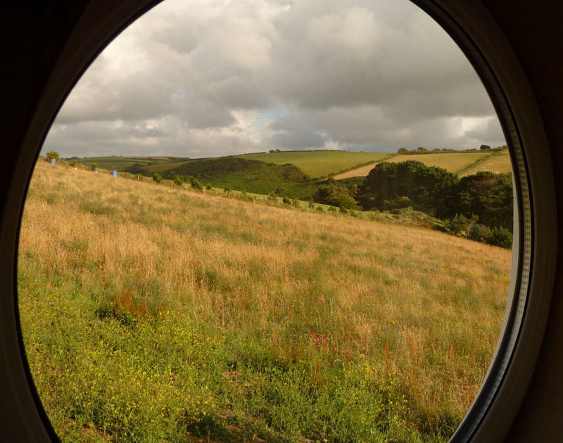 Feature porthole window giving rural views down the valley at Cartway Cabin, a holiday rental  at Port Gaverne near Port Isaac in North Cornwall.