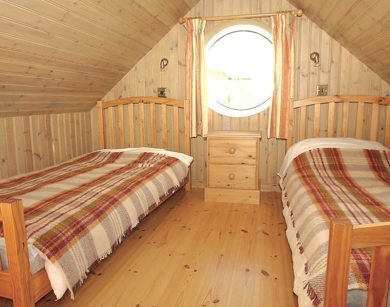 The quirky loft bedroom with twin beds in Cartway Cabin, a unique self catering holiday rental in Port Gaverne near Port Isaac in Cornwall.