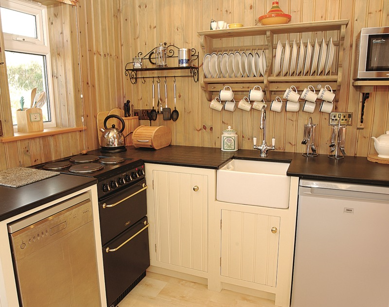 The kitchen area in open plan Cartway Cabin, a self catering holiday rental at Port Gaverne, close to Port Isaac in North Cornwall.