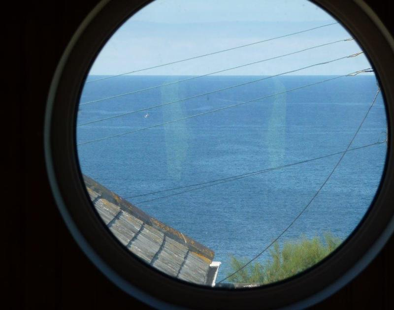 The stunning sea views through the porthole window at Cartway Cabin,  a self catering seaside holiday cottage in Port Gaverne, Cornwall.