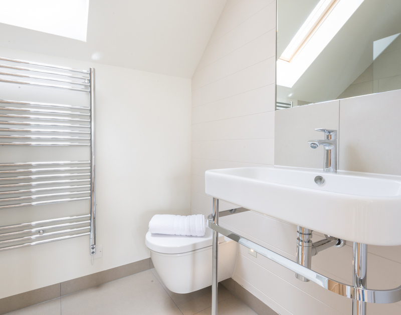 A sleek bathroom of Tregye, a superb self-catering holiday house in Rock, Cornwall, with velux window.