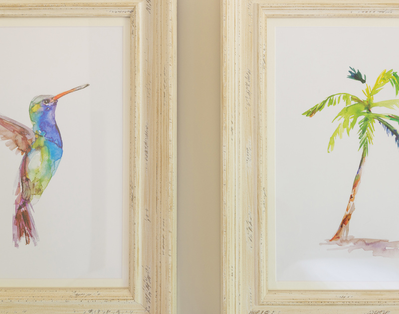 Attractive wall art in a twin room of Tregye, a luxury holiday house in Rock, Cornwall, with hummingbird and palm tree prints.
