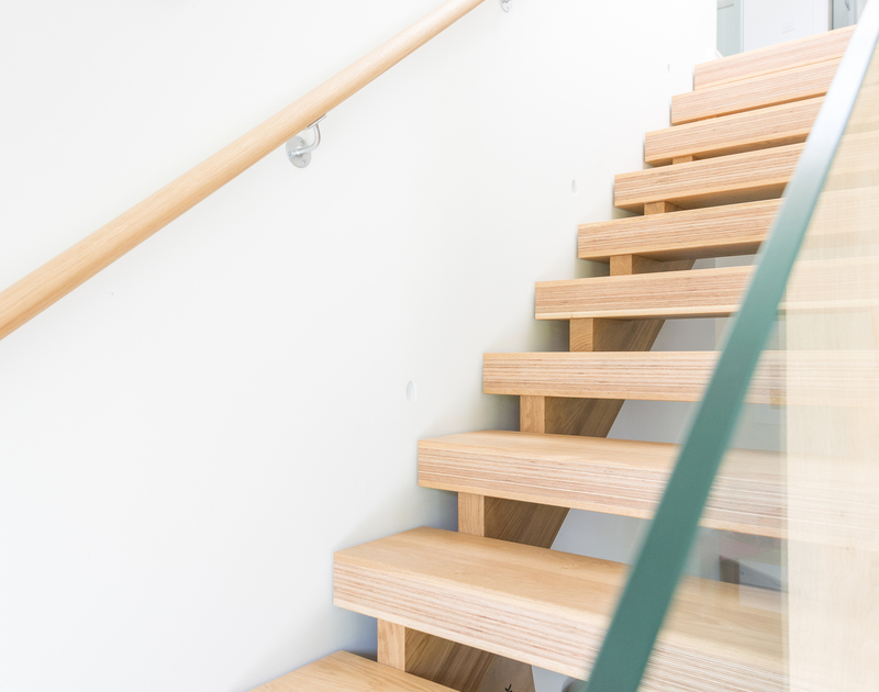 The beautifully designed staircase at Tregye, a luxury holiday house in Rock, Cornwall, with glass balustrade.