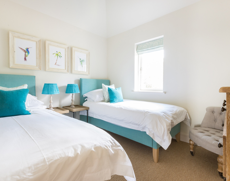 One of two stylish twin bedrooms at Tregye, a luxury holiday house  in Rock, Cornwall, with touches of blue furnishings.