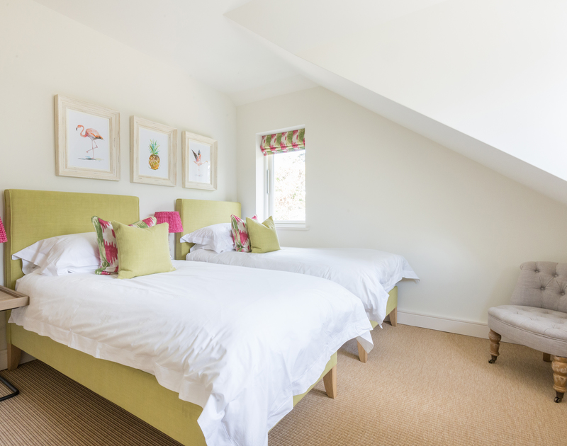 Boutique-hotel style in a twin bedroom of Tregye, a luxury holiday house in Rock, Cornwall, with pops of green and pink furnishings.