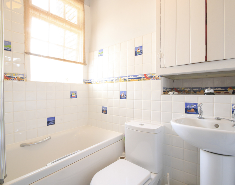 The bright and cheery bathroom in The Fo'c'sle, a self catering holiday cottage to rent in Port Isaac, North Cornwall.