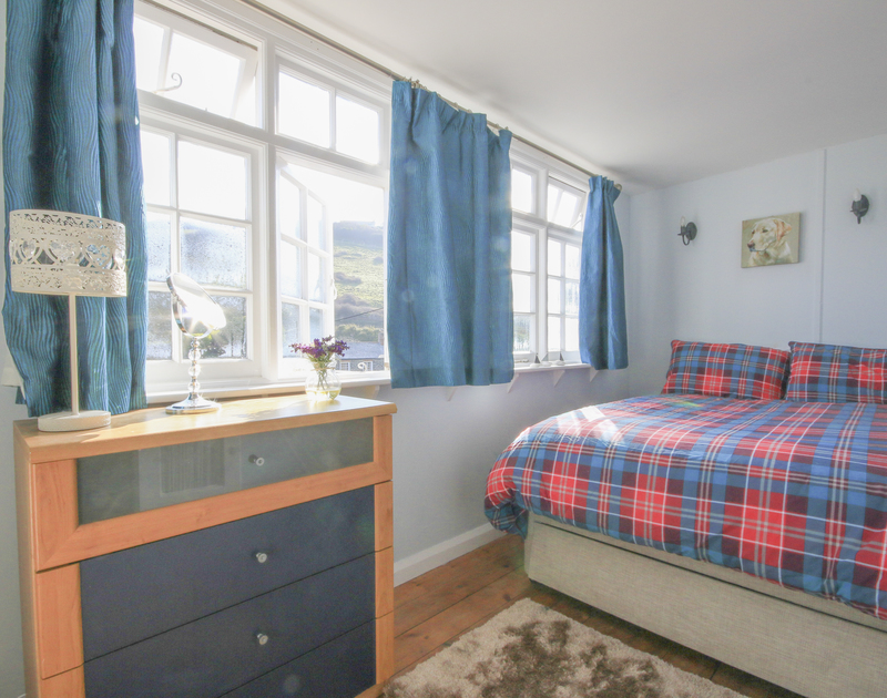 The bright double bedroom with large windows in The Fo'c'sle, a self catering holiday cottage in the heart of Port Isaac, North Cornwall.