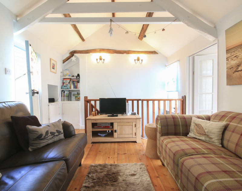 The attractive and tastefully furnished sitting room with vaulted ceiling and warm wooden floorboards in The Fo'c'sle, a holiday cottage to rent in Port Isaac, Cornwall.