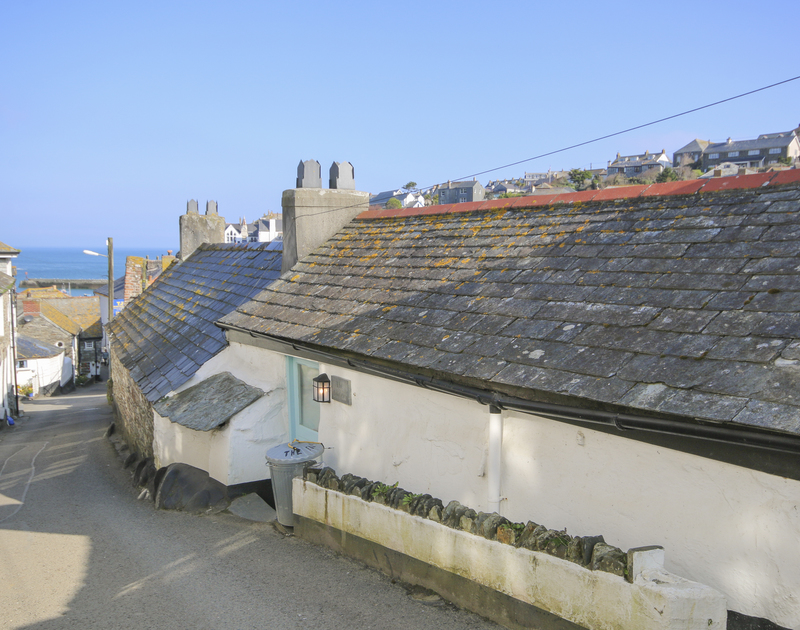 The view down to the harbour on the street at the entrance to The Fo'c'sle, a fishermans cottage for holiday rental in Port Isaac in North Cornwall.
