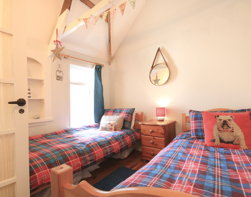 The colourful twin bedroom with vaulted ceilings in The Fo'c'sle, a self catering holiday cottage to rent in Port Isaac, North Cornwall.