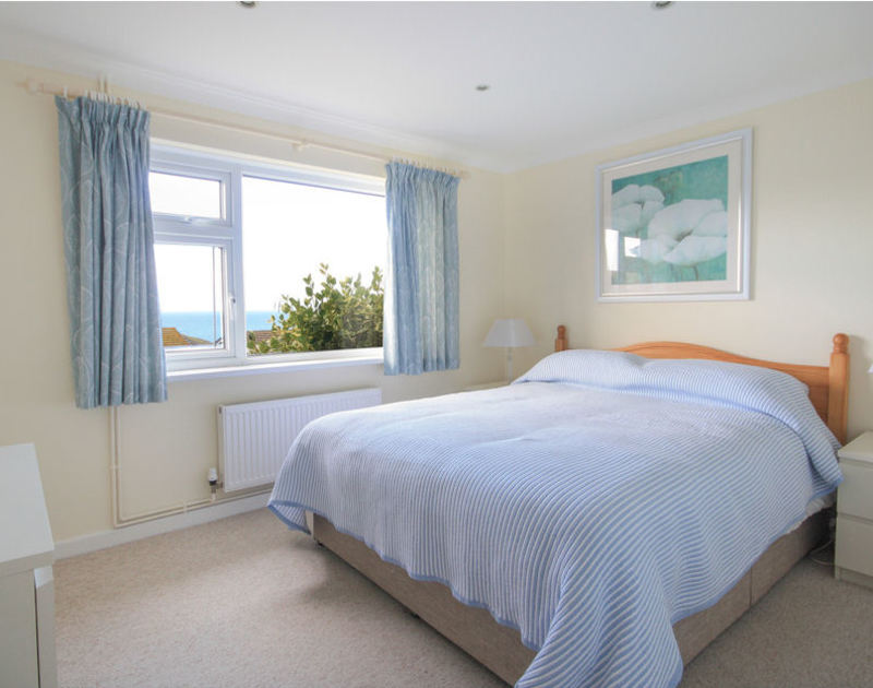The king size bed in the main bedroom with sea views in Sunnybank, a self catering holiday rental in Port Isaac, North Cornwall.