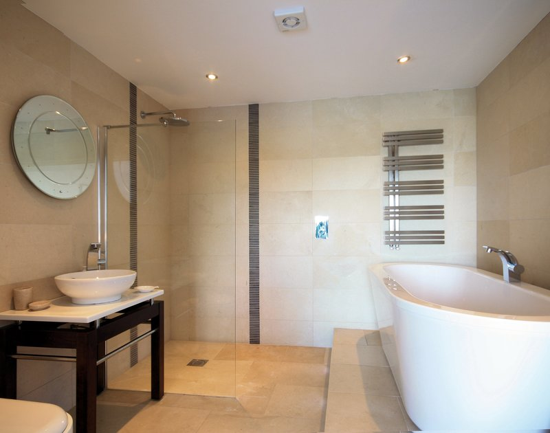 Luxury master ensuite bathroom with a step up to a huge bath tub at The Terrace, a holiday house in Port Isaac, Cornwall,