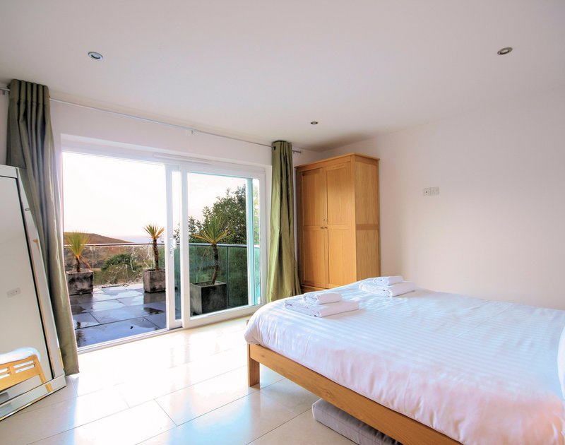 One of three double bedrooms at The Terrace, a luxury holiday house in Port Isaac, Cornwall, with doors to the garden.