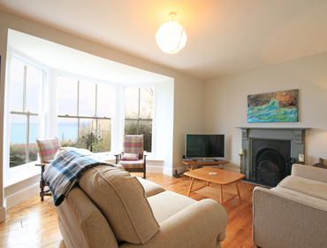 The elegant sitting room with large sash windows,stunning sea and coastal views, attractive working fireplace and warm wooden flooring in Beechmore, a family holiday house to rent in Port Isaac, North Cornwall.