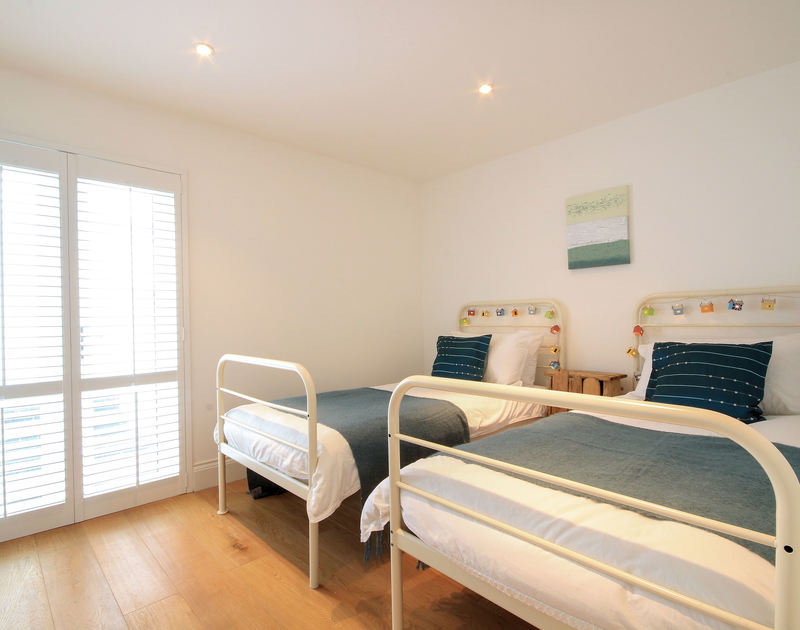 Twin bedroom at Derowen, a self-catering holiday house in Port Isaac, Cornwall with patio doors to lower terrace.