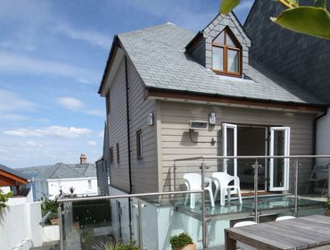 The exterior of Derowen, a self-catering holiday house in Port Isaac, Cornwall, with glass balcony.
