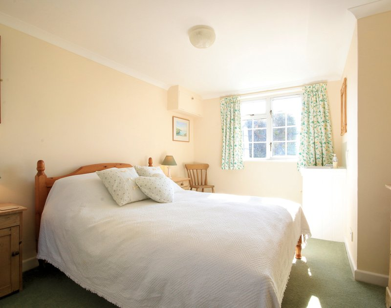 A light-filled double bedroom at Maylands, a self catering holiday property in a tranquil spot above Port Gaverne in North Cornwall.