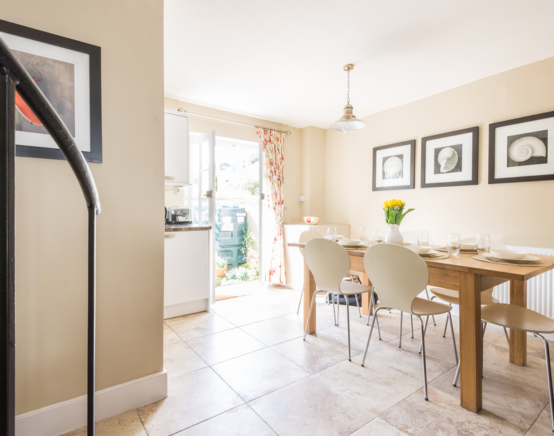Stylish dining area in Dolphin Cottage in Port Isaac, North Cornwall with oak table, tiled floor and door to garden