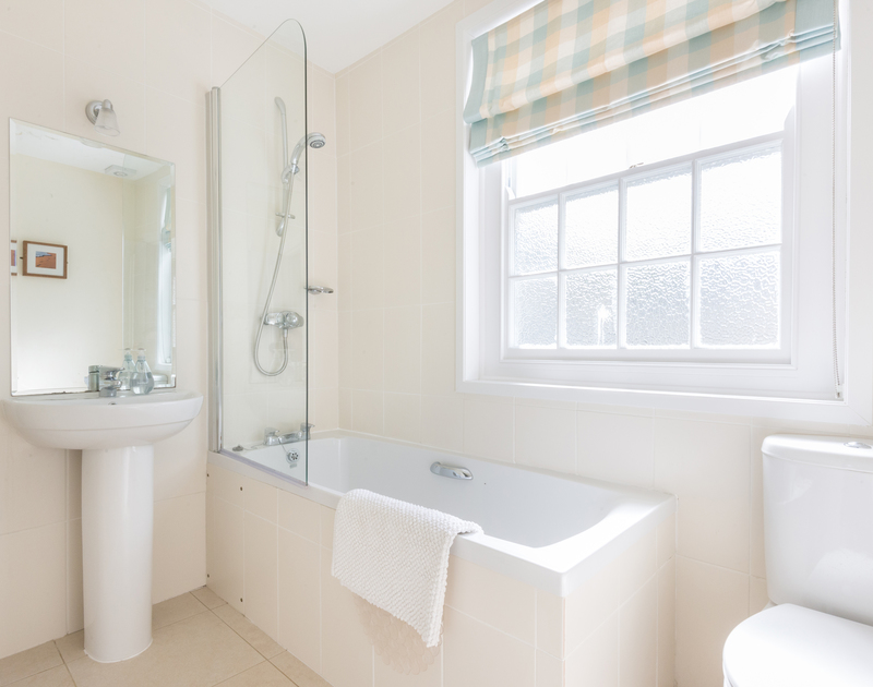 White bathroom suite with light coloured walls in the modern bathroom in Dolphin Cottage, Port Isaac