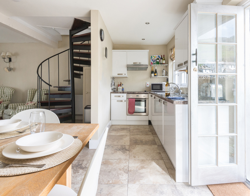 Contemporary and stylish open plan sitting/kitchen/dining room with spiral stairs to the first floor in Dolphin Cottage, Port Isaac
