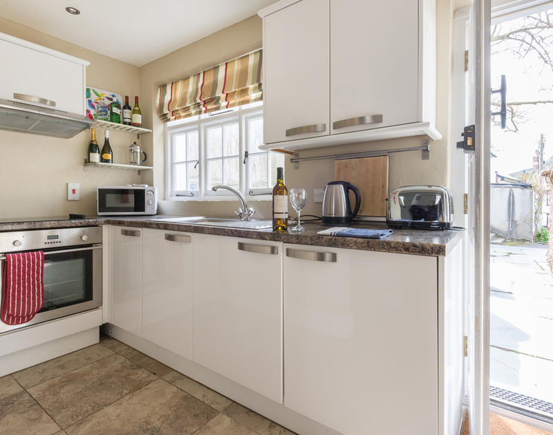 Contemporary kitchen area in Dolphin Cottage in Port Isaac with white cabinets, tiled floor and door to garden