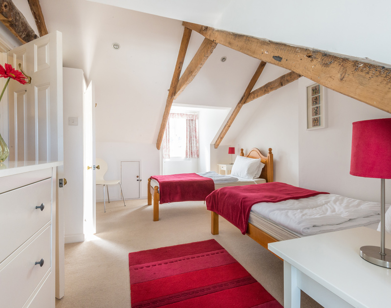 Feature exposed beams to the ceiling of the second floor twin room in Dolphin Cottage, Port Isaac