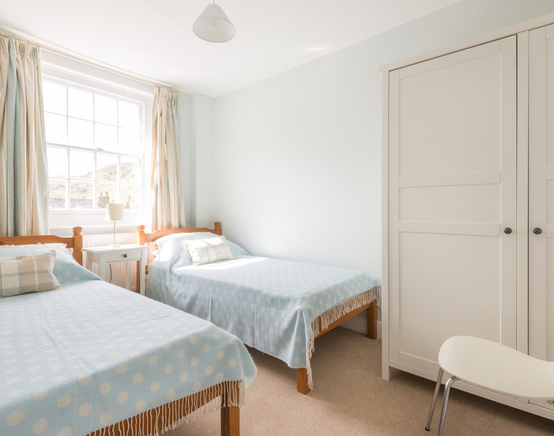 Twin room in Dolphin Cottage, Port Isaac with singe beds, wardrobe and sash window.