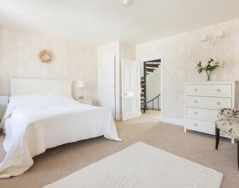 Spacious master bedroom in Dolphin Cottage, Port Isaac with light coloured furniture and decorations and door to landing
