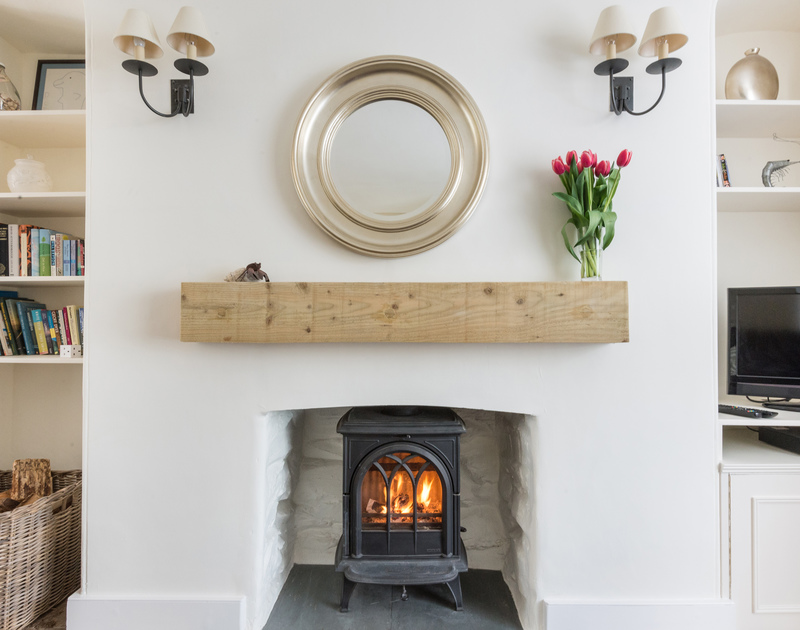 The fireplace in Dolphin Cottage, Port Isaac with woodburning stove and wooden mantle shelf