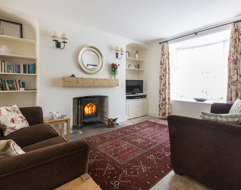 Sitting area in Dolphin Cottage in Port Isaac, North Cornwall, with tiled floor, woodburning stove and comfortable sofas.