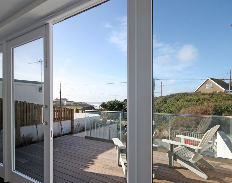 The raised, wooden deck of The Beach House, a holiday house to rent in Polzeath, Cornwall, with its coastal views.