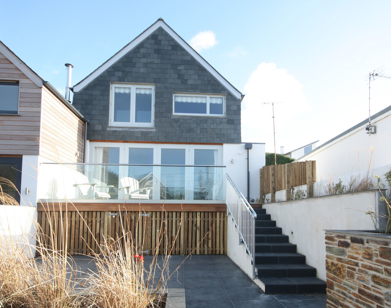 The front exterior view of The Beach House, holiday let in Polzeath, Cornwall, with steps up to its raised deck.