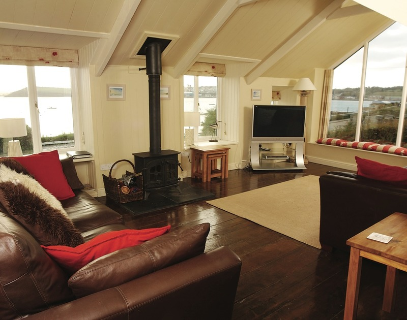 The comfortable sitting room with wood burner and stunning Camel Estuary views in The Cottage, a self catering holiday rental in Rock, North Cornwall.