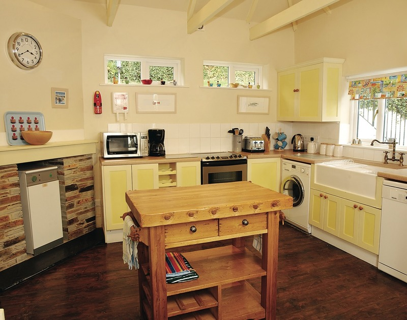The bright, welcoming kitchen with butchers block in The Cottage, a self catering holiday rental in Rock, North Cornwall.