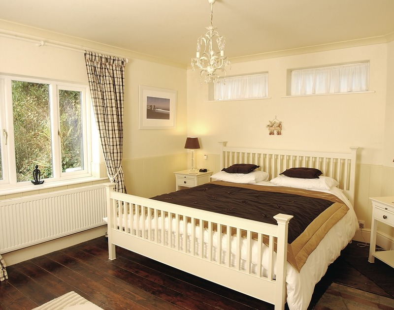 The attractive bedroom with wooden floorboards and super king bed in The Cottage, a self catering holiday rental in Rock, Cornwall.