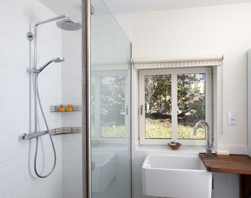 The practical wetroom of The Old Granary, a holiday house in Rock, Cornwall, with a walk-in shower and butler sink.