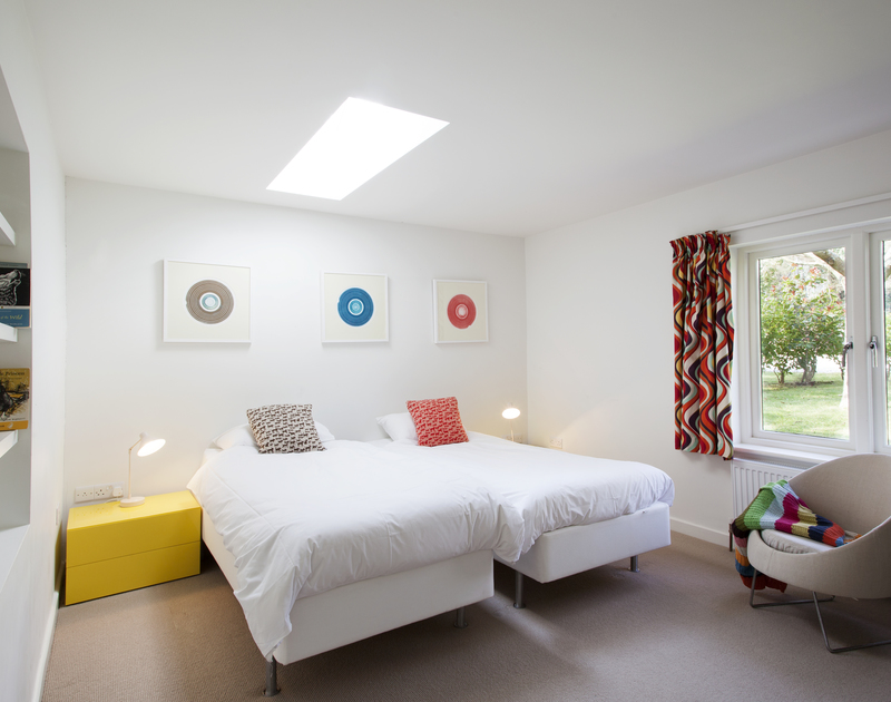 Pops of colour decorate this bedroom at The Old Granary, a holiday rental in Rock, Cornwall, with zip and link twin beds.