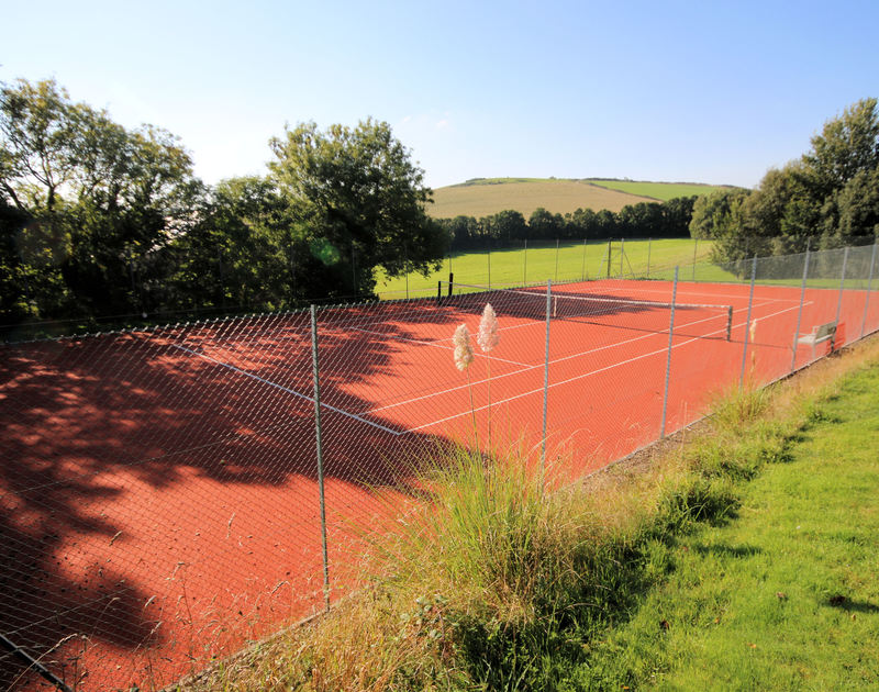 The shared, hard-surface tennis court at The Old Granary, a holiday house in Rock, Cornwall