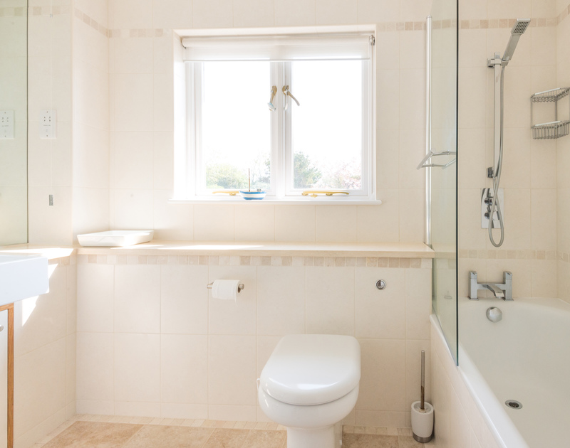 Another family bathroom with a bath and shower combined at Ragleighs, a luxury self catering, pet friendly holiday house above Daymer Bay in Cornwall.