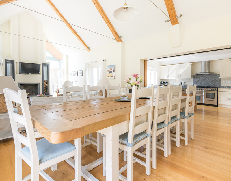 A beautiful wood dining table, perfect for entertaining, and part of the open plan sitting room, dining room and kitchen at Ragleighs, a luxury holiday house above Daymer Bay in North Cornwall.