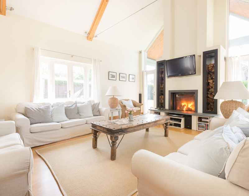 A bright, neutral, stylish sitting room with a fantastic woodburner and views across the garden at Ragleighs, a holiday house to rent in Daymer Bay, Cornwall.