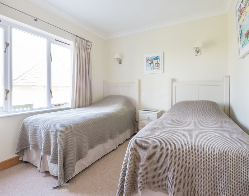 A neutral twin bedroom in Ragleighs, luxury self catering holiday accommodation near Daymer Bay beach in North Cornwall.