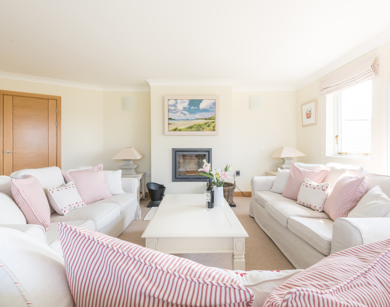 The upstairs sitting room with a woodburning fire and views out across the Camel Estuary at Ragleighs, a luxury holiday house set above Daymer Bay in North Cornwall.