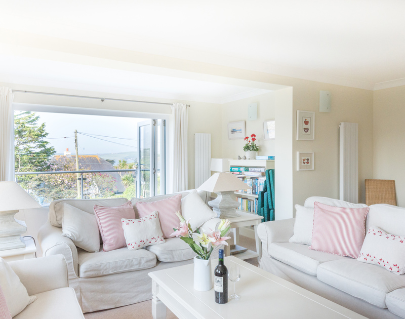 The upstairs sitting room, with a private balcony with fantastic views out towards the Camel Estuary at Ragleighs, luxury self catering holiday accommodation set above Daymer Bay in North Cornwall.