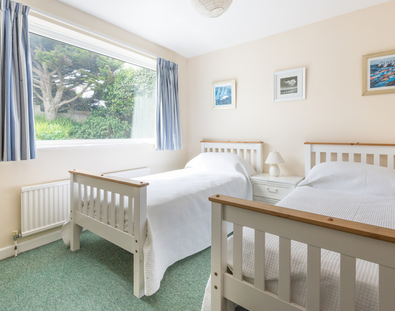 Bright and airy twin room with garden views at Trevega, a holiday house in Polzeath, Cornwall