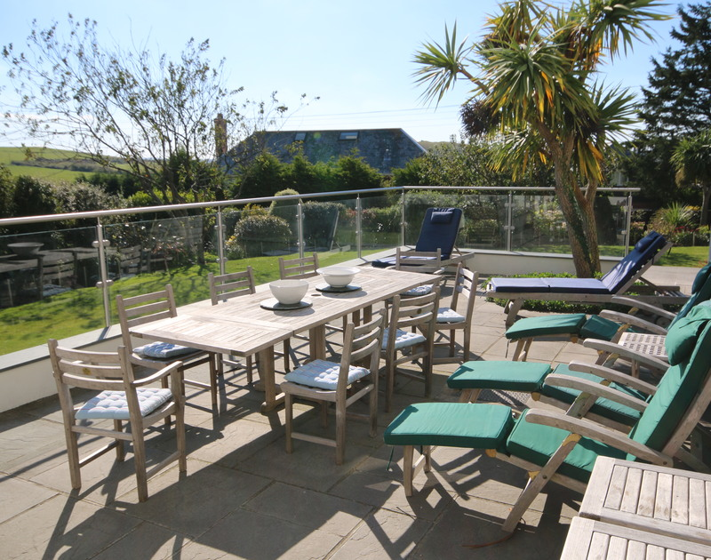 A glass-protected sun terrace with a dining area, comfortable sun loungers and a barbeque, making it the perfect place to enjoy the sunshine at Ragleighs, a self catering holiday house set above Daymer Bay in North Cornwall.