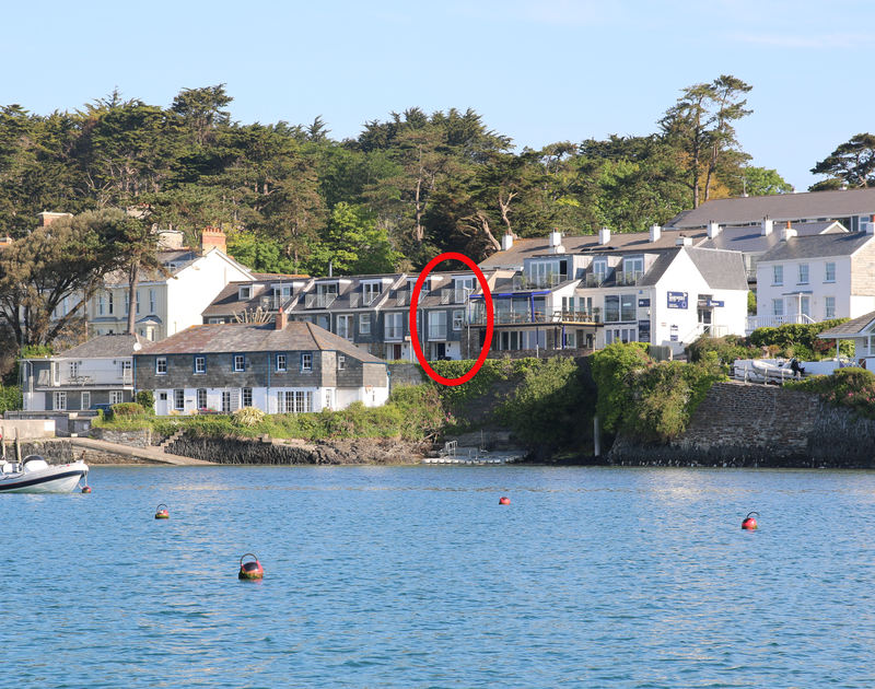 A view of Slipway 6, an end-of-terrace cottage to rent in Rock, Cornwall, from a boat on the estuary showing its prime position near the shore.