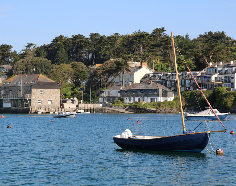 A beautiful shot taken from the water of a traditional sailing boat in the foreground of 2 Quay Cottage, a holiday house with a fantastic location next to the sailing club and the shore at Rock, North Cornwall
